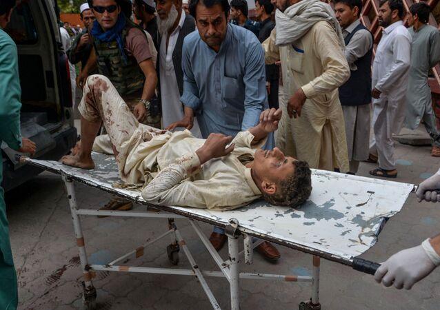 Ferido em explosão de mesquisa na província de Nangarhar, no Afeganistão, é carregado por voluntários