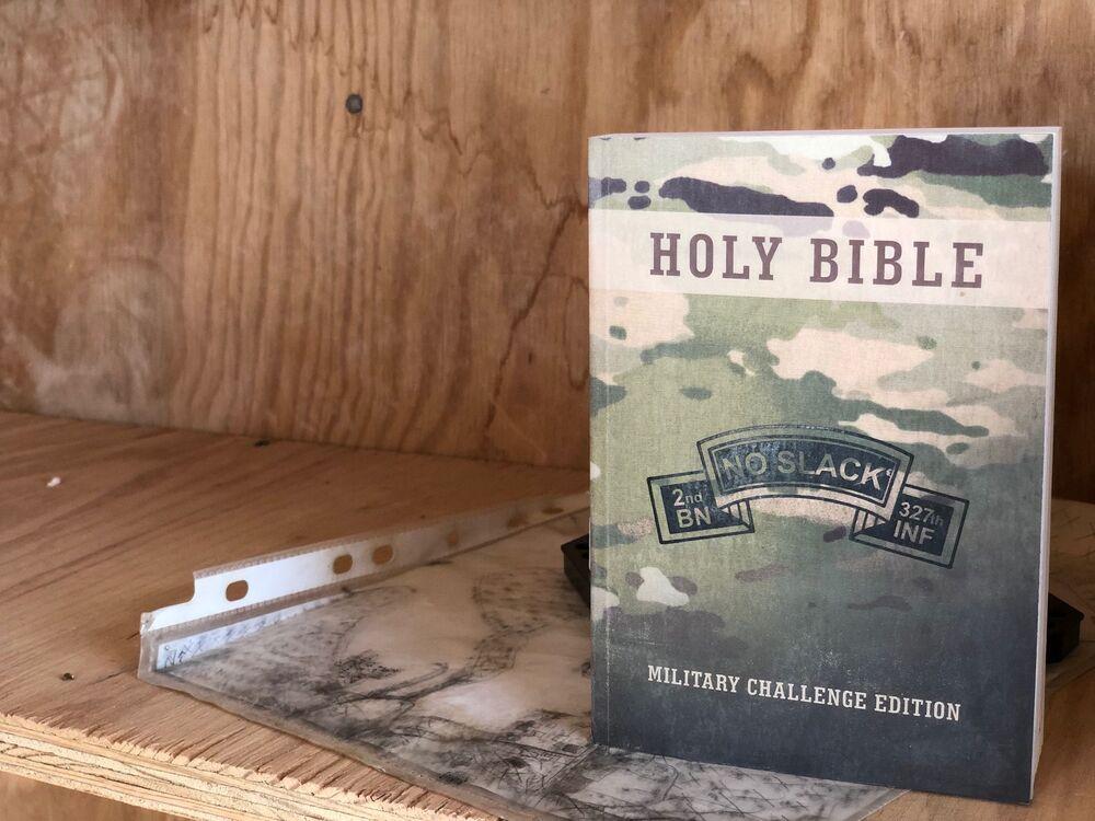 Bíblia e mapa sobre estante de madeira na abandonada base de coordenação aérea do Exército dos EUA em Dadat, Manbij, no nordeste da Síria