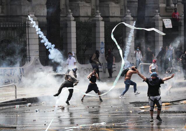 Manifestantes são atingidos por bombas de gás lacrimogêneo durante protestos e depredações no Chile