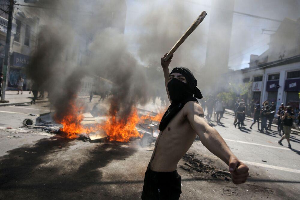 Participante de protesto no Chile monta barricadas para evitar tropa de choque