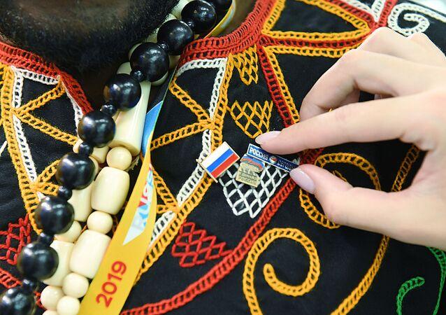 Participante do Fórum Rússia-África, em Sochi, recebe botton com a bandeira da Rússia e com o logotipo da Rossiya Segodnya, em 24 de outubro de 2019