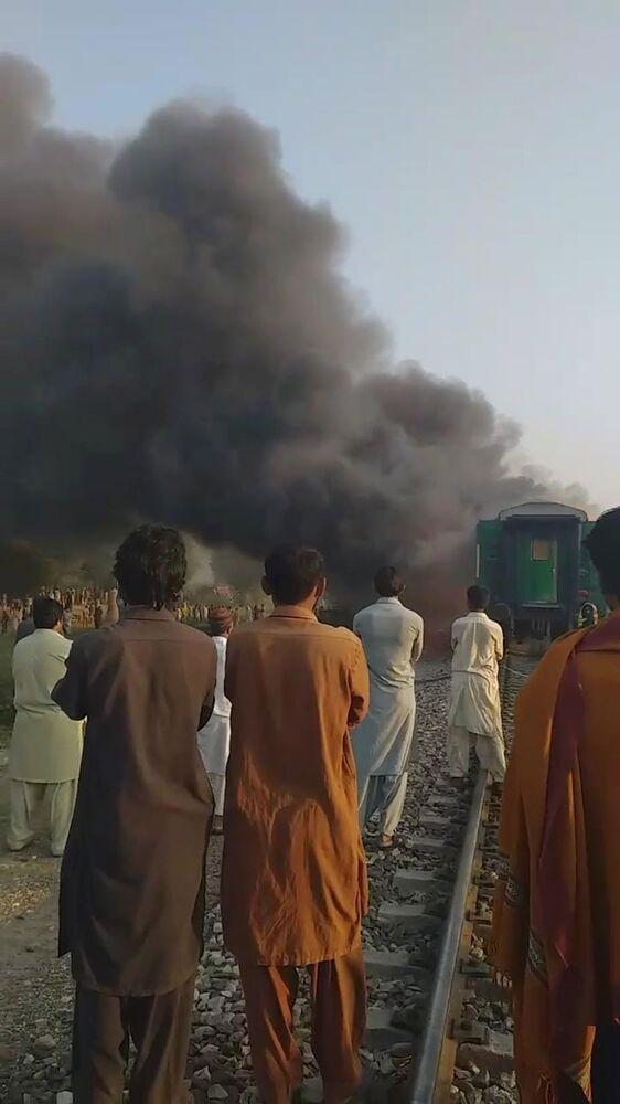 Paquistaneses observam o incêndio ocorrido no interior do trem a partir de outro ângulo