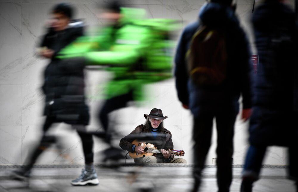 Músico de rua russo Sergei Sadov se apresentando na entrada de uma estação de metrô de Moscou
