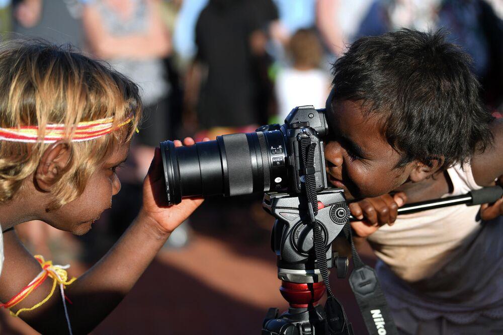 Crianças brincam com câmera fotográfica no parque Uluru-Kata Tijuta, Austrália