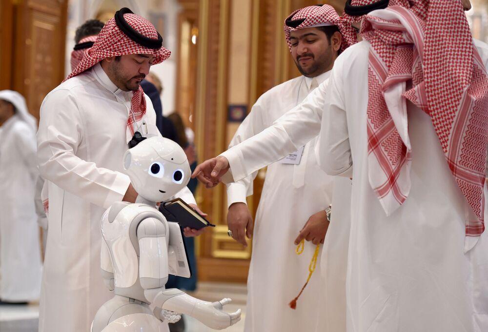 Visitantes do fórum Future Investiment Initiative ao lado de um robô em Riad, Arábia Saudita