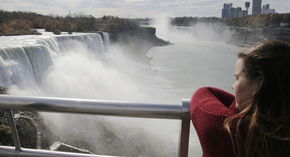 Uma turista olhando para as Cataratas do Niágara na fronteira entre os EUA e o Canadá