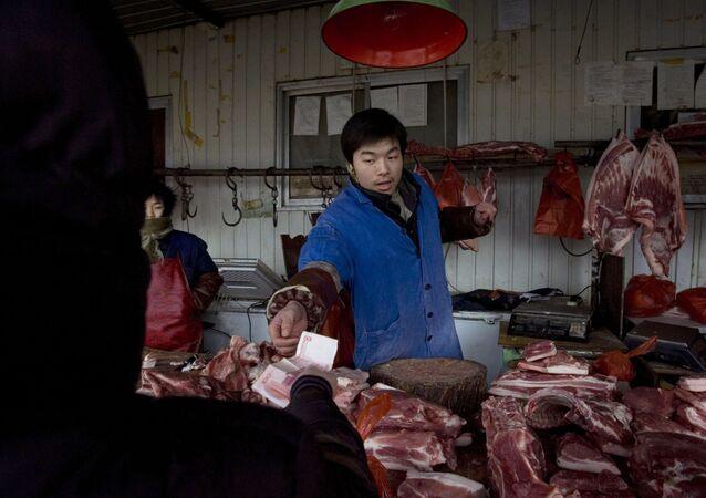 Açogueiro chinês devolve troco em mercado de rua. O dinheiro em papel está com os dias contados na China