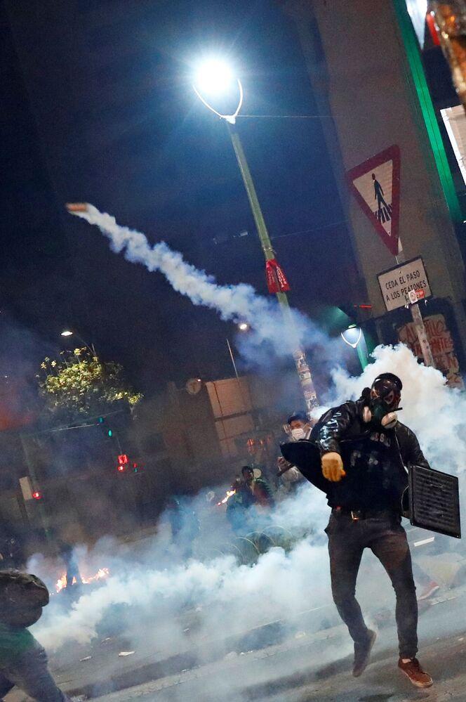 Manifestante, protegido com máscara de gás, atira bomba de gás lacrimogênio durante protestos em La Paz, ocorridos no dia 31 de outubro de 2019
