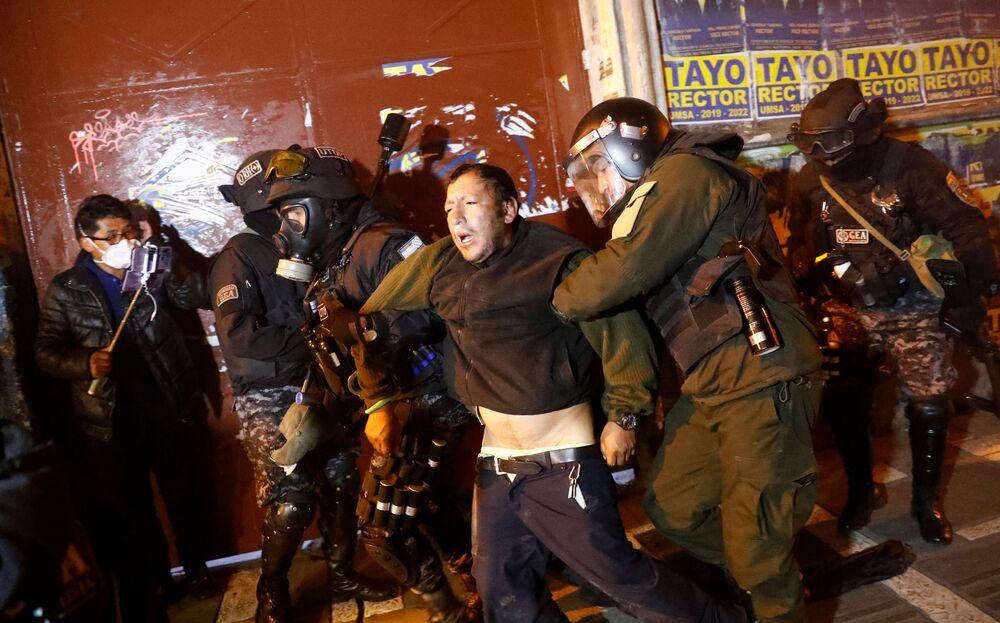 Homem ferido é acudido pela polícia, durante conflito entre manifestantes na cidade de La Paz, nesta terça-feira (5)