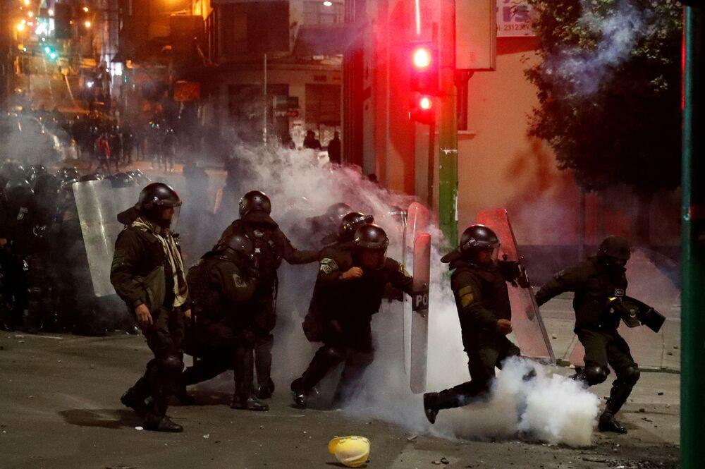 Tropa de choque tenta afastar bomba de gás lacrimogênio atirada por manifestante, durante confronto em La Paz, no dia 5 de novembro de 2019