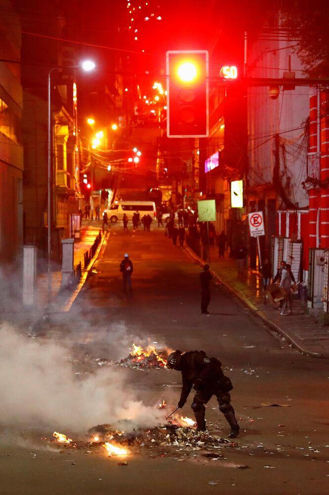 Tropa de choque observa fogo ateado durante confrontos entre manifestantes que acatam os resultados das eleições e manifestantes que acusam o governo de fraude eleitoral, em La Paz, em 5 de novembro de 2019