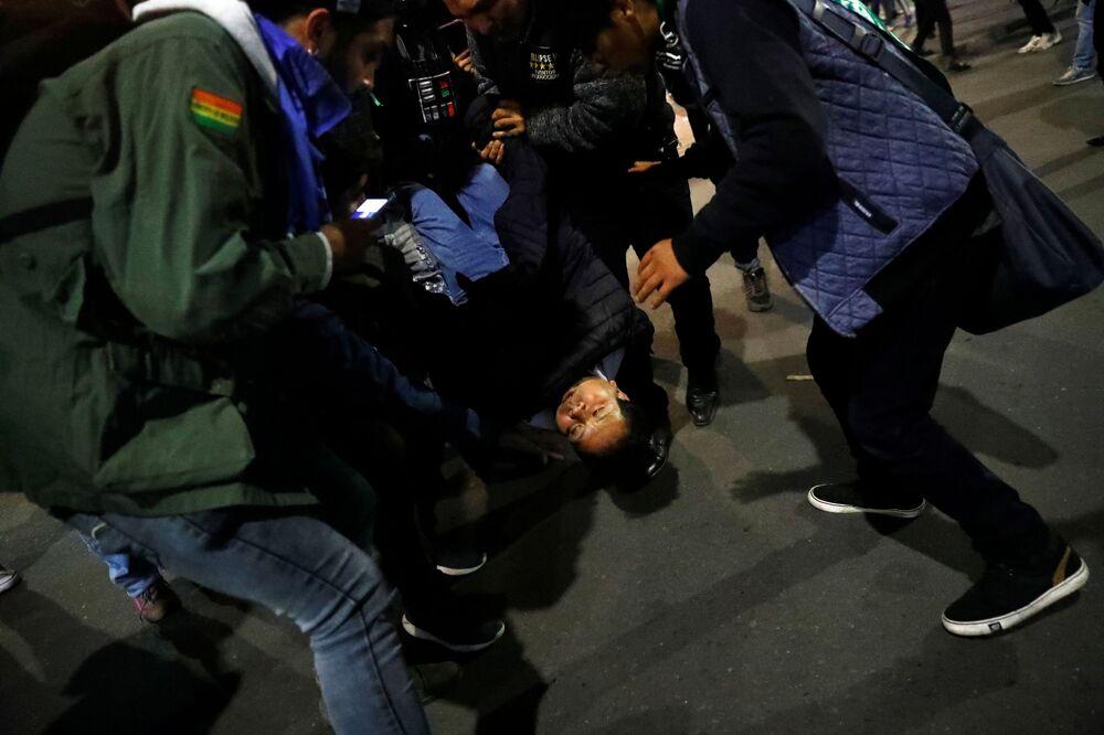 Grupo acode uma mulher durante confronto entre manifestantes que eclodiu na cidade boliviana de La Paz, nesta terça-feira (5)