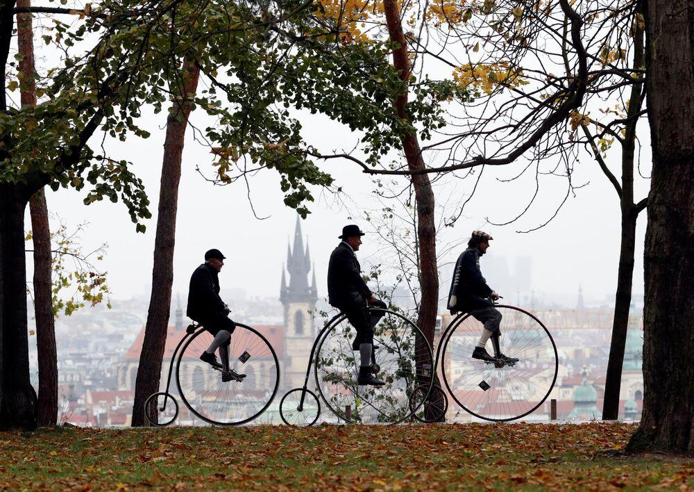 Participantes de um evento de ciclismo com trajes antigos em Praga, República Tcheca