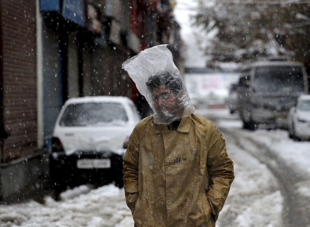 Homem cobre a cabeça com um saco plástico enquanto cai neve em Srinagar, na Caxemira controlada pela Índia