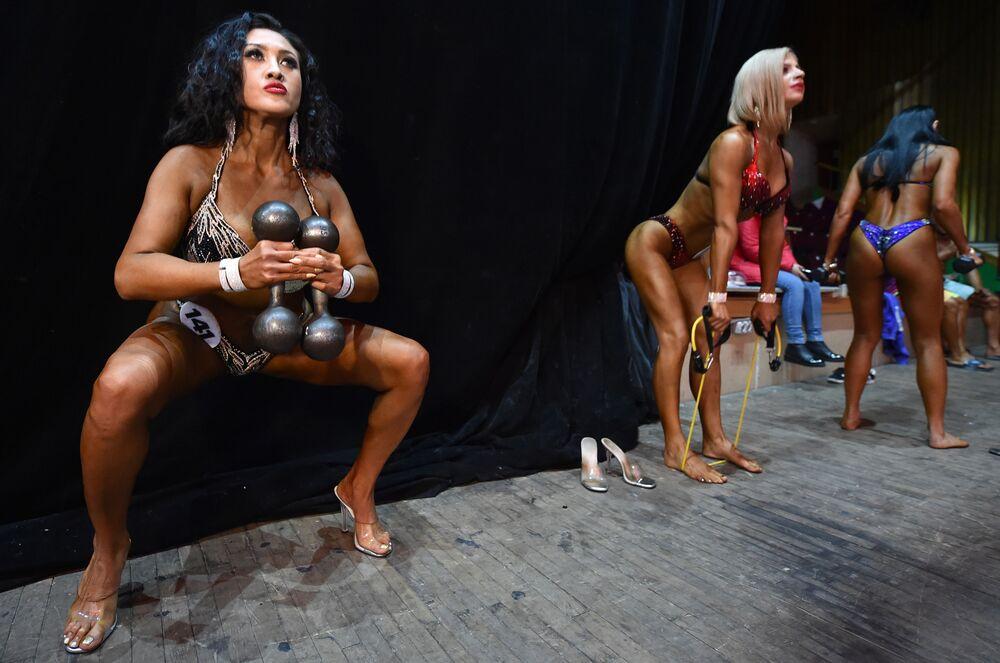 Mulheres fisiculturistas se aquecendo antes da competição Bikini Fitness Bodybuilding Contest em Bishkek, Quirguistão