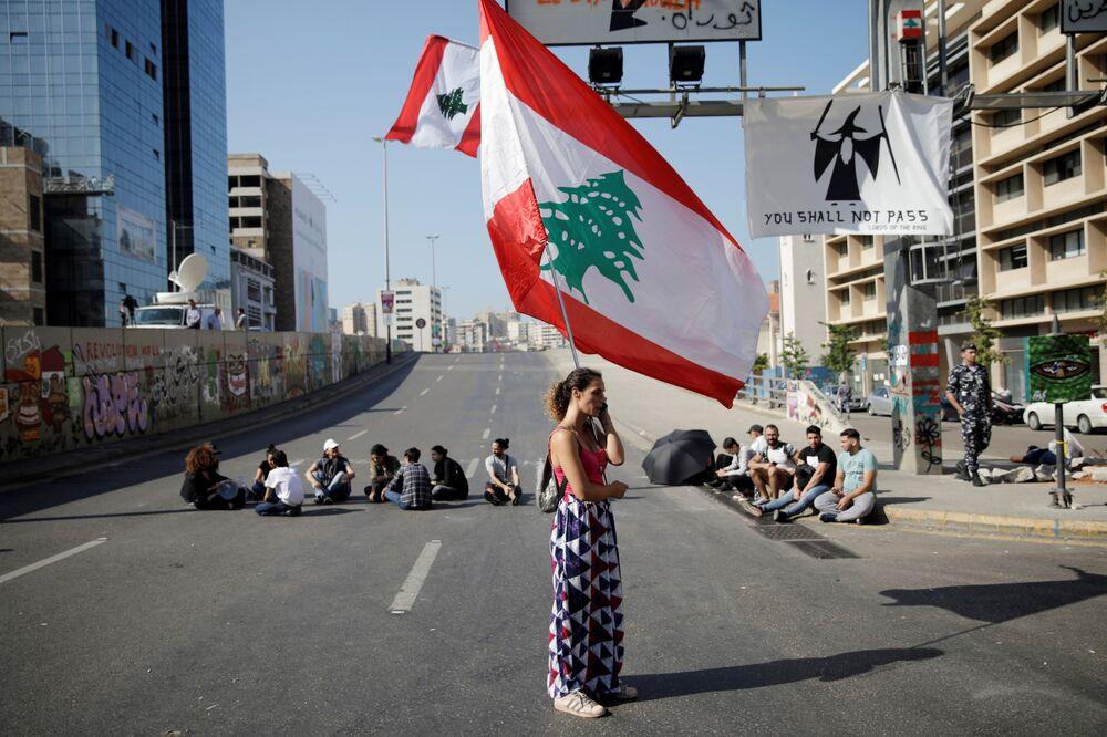 Mulher com a bandeira do Líbano participa de um bloqueio de rodovia no país árabe durante manifestações contra o governo em Beirute