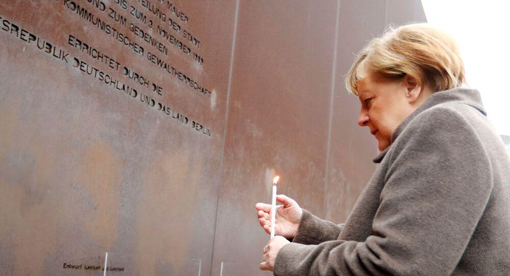Chanceler alemã Angela Merkel deposita uma vela durante as celebrações dos 30 anos da queda do Muro de Berlim