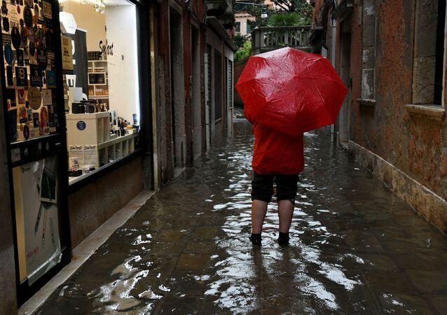Turista passeia com guarda-chuva por uma das ruas de Veneza