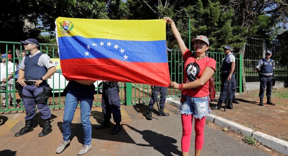 Apoiantes do presidente da Venezuela, Nicolás Maduro, seguram bandeira diante da embaixada da Venezuela em Brasília, Brasil, 13 de novembro de 2019