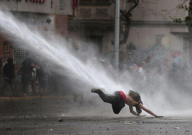 Manifestante é atingido por jato de água durante protesto contra o governo chileno, em Santiago, Chile, 11 de novembro de 2019