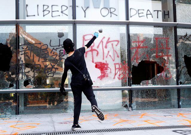 Manifestante atira pedra em um prédio da Universidade Politécnica de Hong Kong