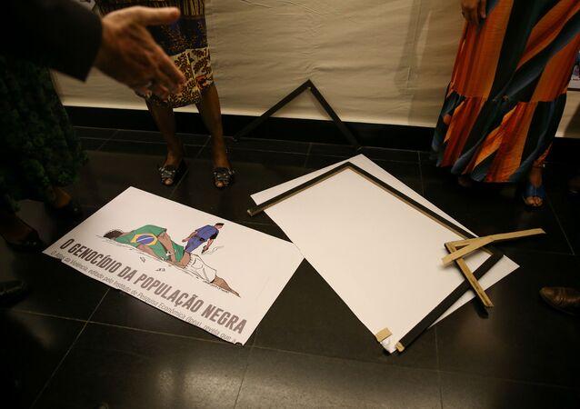 Placa com charge que faz parte de uma exposição sobre o dia da Consciência Negra na Câmara, é quebrada pelo deputado Coronel Tadeu (PSL-SP). A charge retrata um negro algemado caído no chão e um policial com uma arma fumegante se afastando