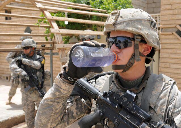 Soldado americano bebe água durante patrulha cerca da da cidade iraquiana de Rizgari