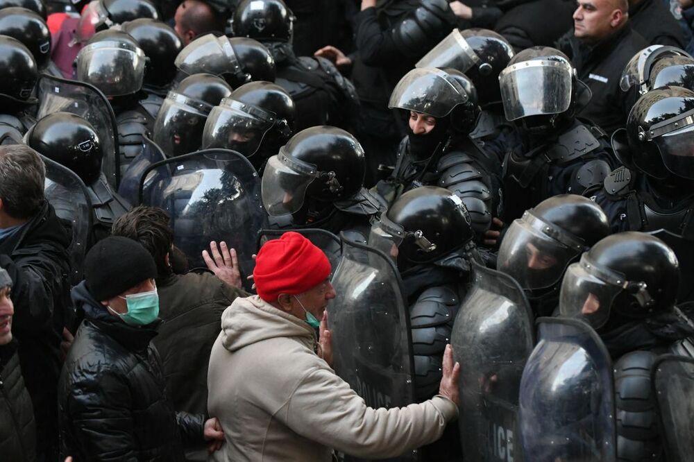 Forças policiais georgianas dispersando manifestantes da oposição ao lado do prédio do parlamento do país