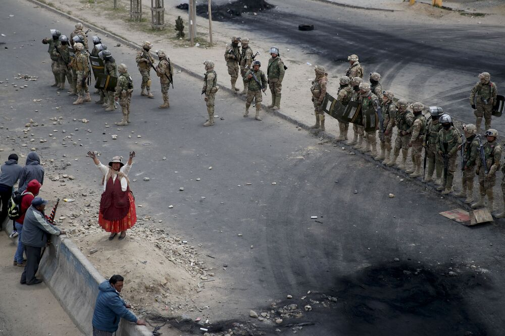 Apoiadores do ex-presidente boliviano Evo Morales ao lado de soldados