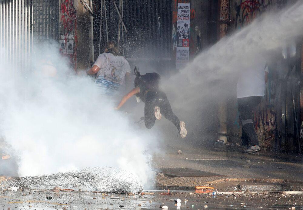 Manifestante é jogada no chão por um canhão de água da Polícia do Chile durante manifestação na capital Santiago