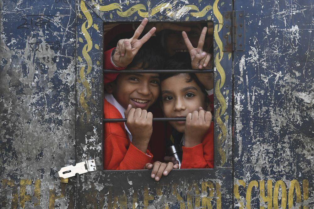 Crianças sorriem durante caminho de volta para casa após a escola dentro de um riquixá na capital indiana de Nova Deli