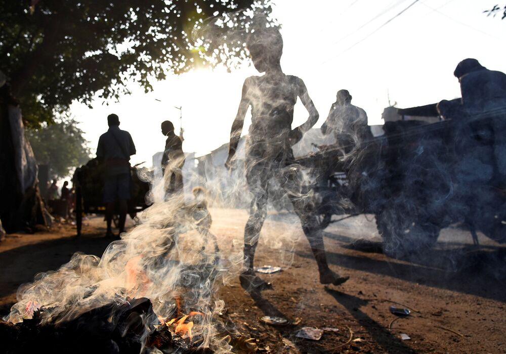 Pessoas passam em frente a um monte de lixo em chamas na cidade indiana de Calcutá