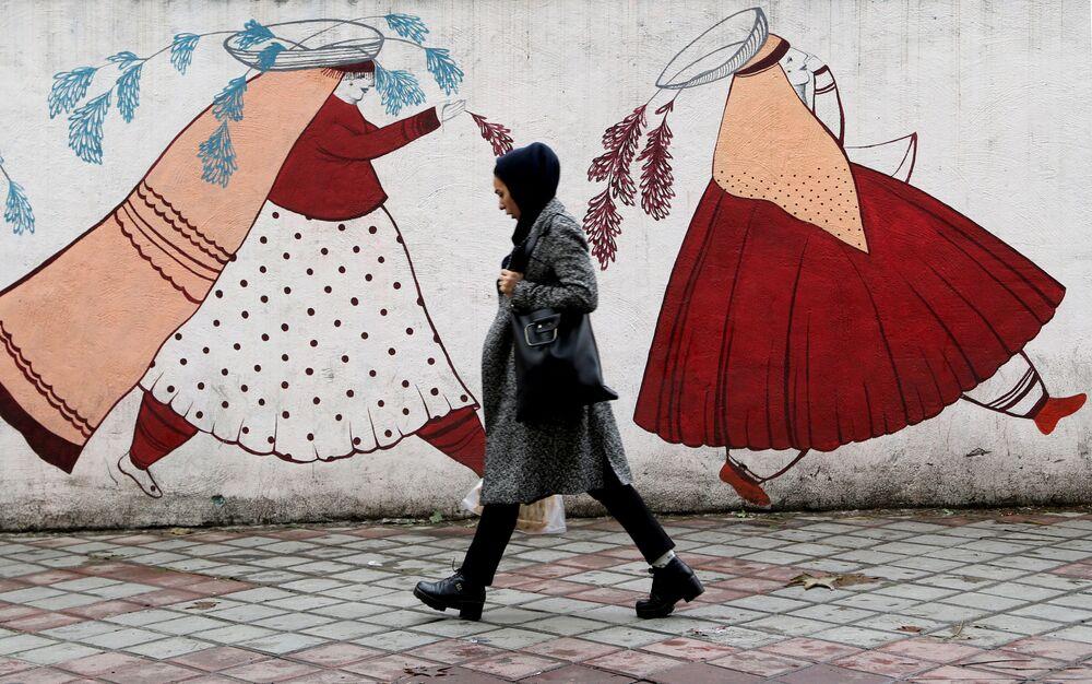 Mulher iraniana passa em frente a muro com desenho de mulheres camponesas do país