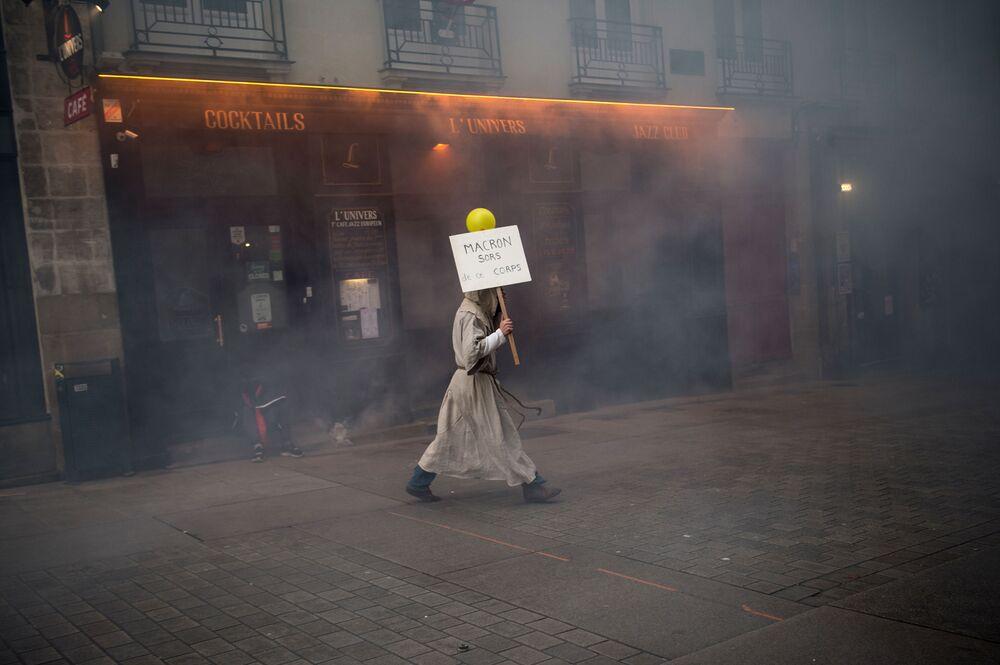 Homem vestido de monge carrega placa com os dizeres Macron saia deste corpo na cidade francesa de Nantes
