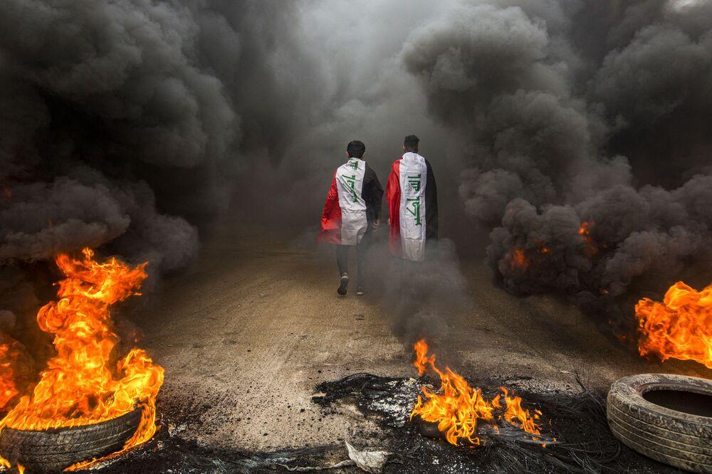 Manifestantes contra o governo iraquiano caminham com bandeiras do país entre chamas na cidade iraquiana de Basra