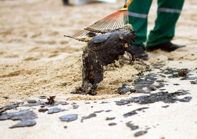 Voluntário retira óleo das areias da praia de Barra de Jacuipe em Camaçari, na Bahia