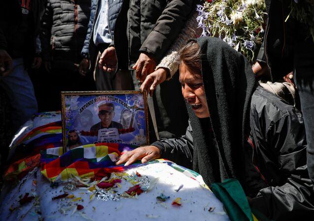 Mulher chora ao lado do caixão de uma das vítimas nos protestos em La Paz, na Bolívia