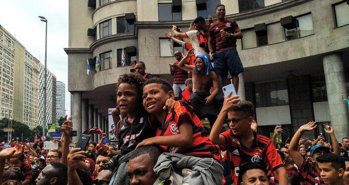Crianças e adultos festejando juntos a conquista do Flamengo na Libertadores