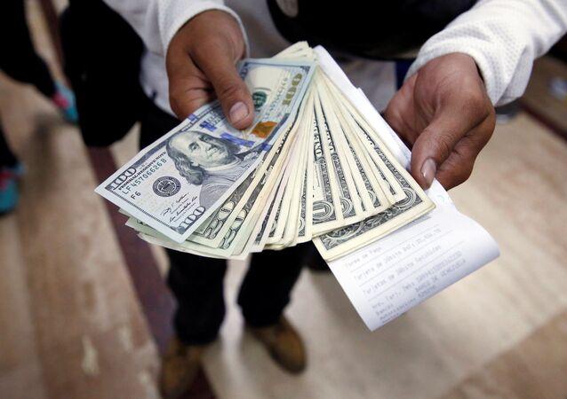 Homem posando com dólares depois de comprá-los em uma casa de câmbio em Caracas (Foto de arquivo)