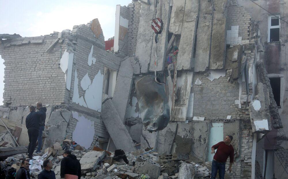 Guindaste remove entulho dentre escombros de prédio que desabou durante o terremoto na cidade albanesa de Thumane