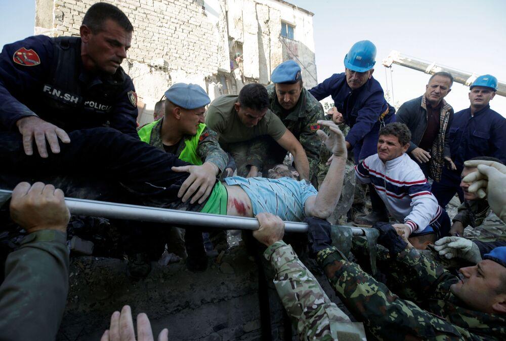 Homem é carregado em uma maca por socorristas após terremoto atingir edifício em Thumane, na Albânia