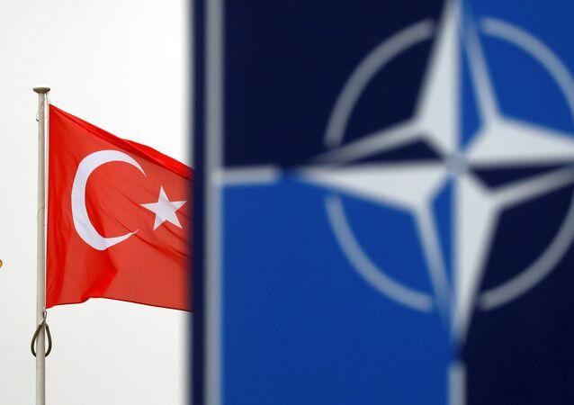 Bandeira turca esvoaçando ao lado do logótipo da OTAN no quartel-general da aliança em Bruxelas