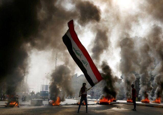 Manifestante com a bandeira do Iraque durante ação de protesto na cidade de Najaf, Iraque