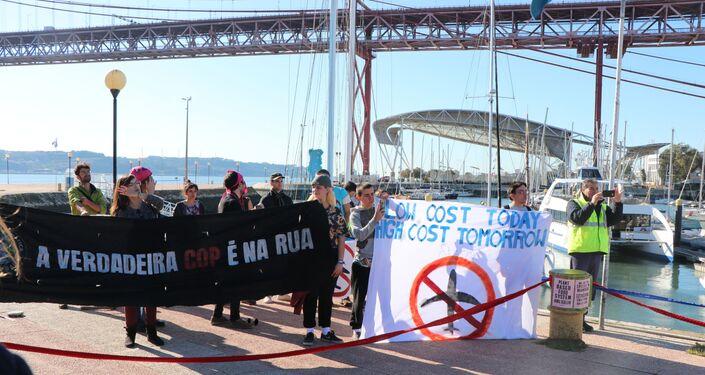 Manifestantes exibem faixas de protestos na recepção de Greta Thunberg em Lisboa