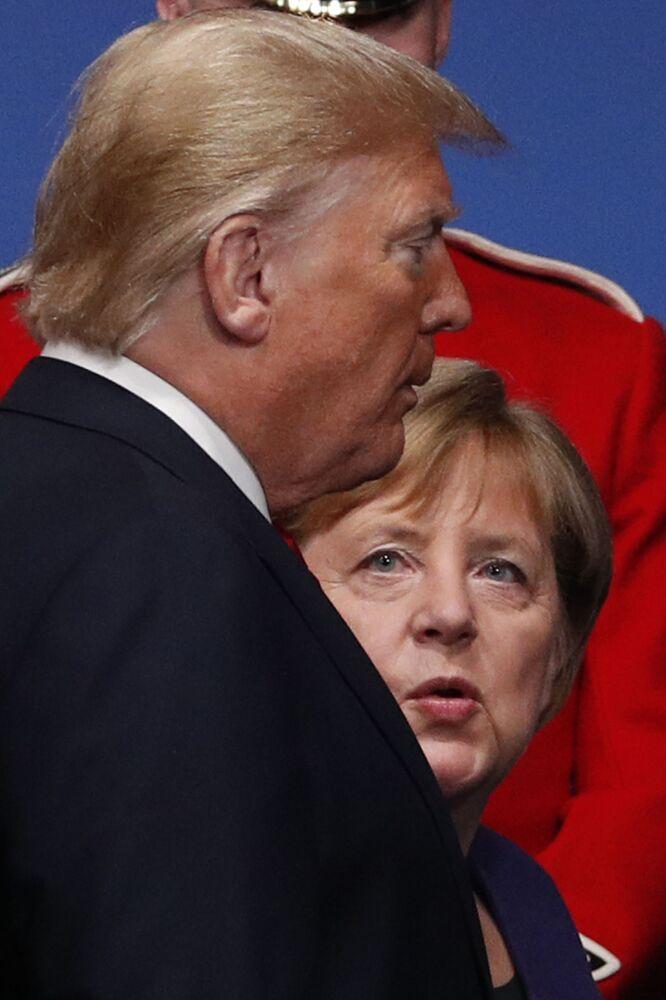 Presidente dos Estados Unidos e chanceler alemã após fotografia em grupo com outros líderes de Estados-membros da OTAN.