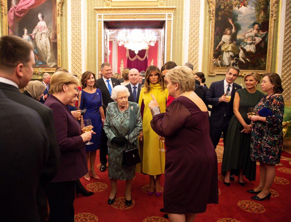 Chanceler alemã e primeira-dama dos Estados Unidos durante encontro com a rainha do Reino Unido no Palácio de Buckingham.