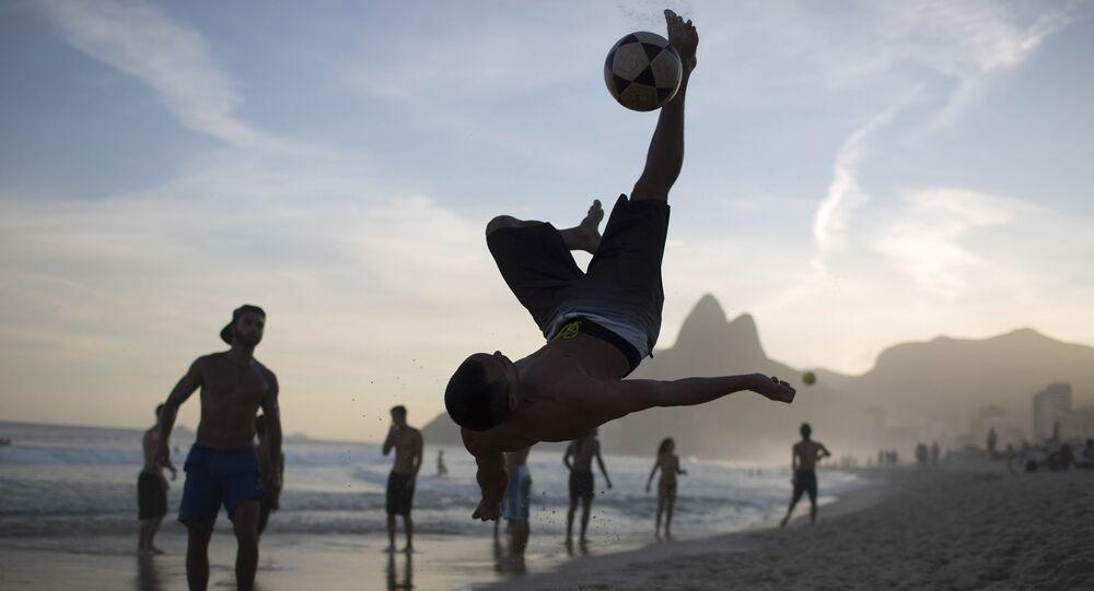 Homem joga futebol na praia de Ipanema, no Rio de Janeiro.
