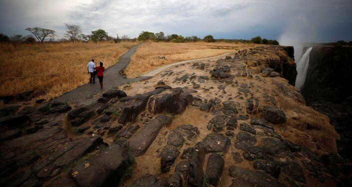 Visitantes caminham perto das cataratas de Vitória, Zimbabué, em 4 de dezembro de 2019