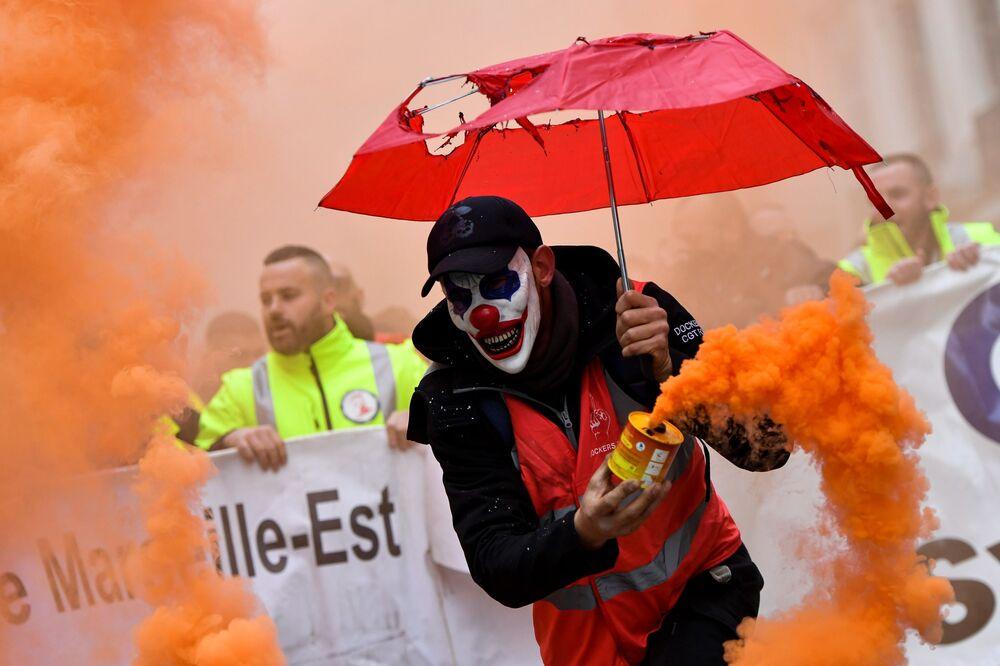 Homem em máscara de palhaço com bomba de fumaça durante protestos contra reforma do sistema de aposentadoria na cidade de Marselha, França