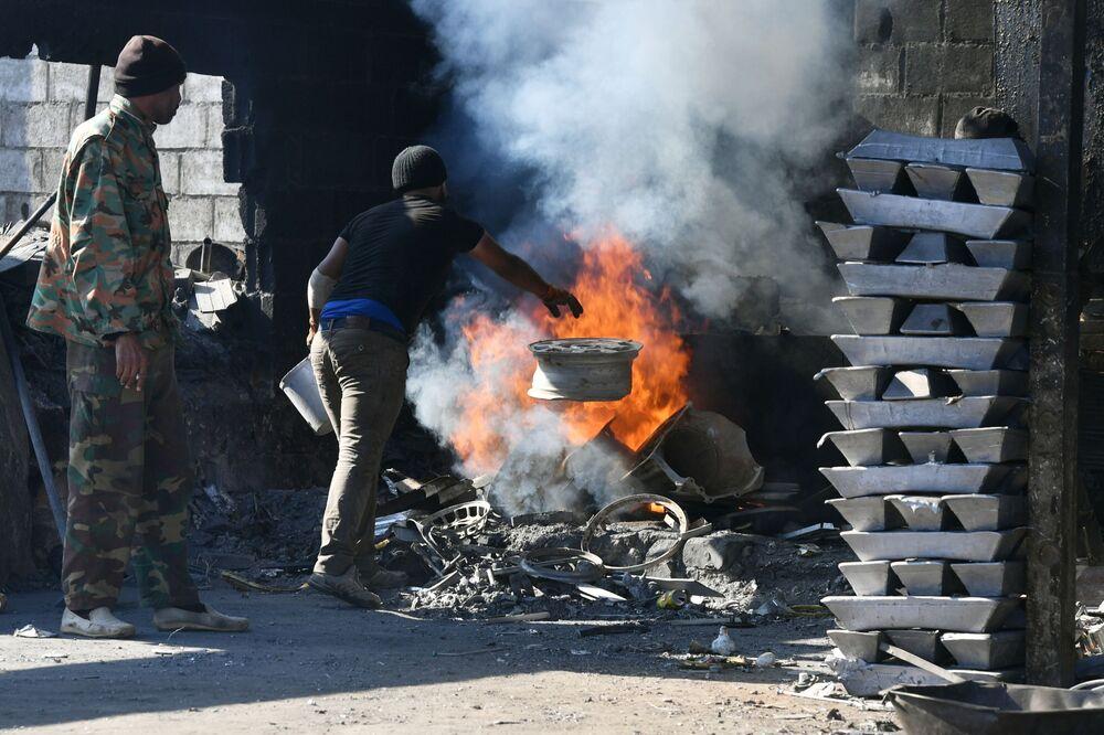 Operários fundem alumínio em uma fábrica privada perto da cidade de Damasco, Síria